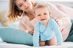 Mother and happy little child looking at camera together while relaxing. In bed royalty free stock photography