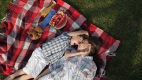 Mother and happy little son speak and laugh lying on grass. Beautiful mother and happy little son speak and laugh lying on red checkered blanket close vertical stock footage