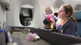 Mother with a happy small child on the plane a woman holds a baby who takes a toy from a special bassinet stock video footage