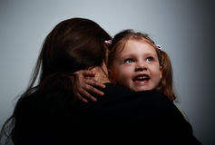 Mother and happy smiling daughter hugging on dark Royalty Free Stock Images