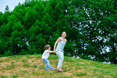 Mother and happy son playing in summer park stock image