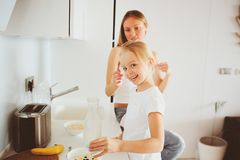 Mother having breakfast with kid daughter at home in modern white kitchen royalty free stock photos