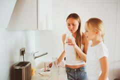 Mother having breakfast with kid daughter at home in modern white kitchen stock images