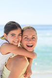 Mother having daughter a piggyback at the beach Stock Images