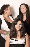 Mother having fun with daughters. Mother with tattoos, piercings and dreadlocks has some fun with her two daughters on white background containing some shadow Royalty Free Stock Photos