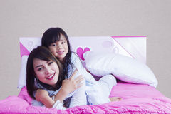 Mother having fun with her daughter on bed Stock Photos