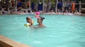 Mother having fun with little girl in the pool. stock footage