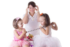 Mother having headache of two daughters quarreling Royalty Free Stock Photos