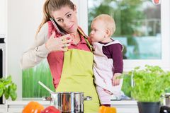 Mother having phone conversation during cooking and holding baby Stock Photo
