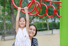 Mother help her daughter to playing on gymnastic ring on playground outdoor stock image