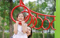 Mother help her daughter to playing on gymnastic ring on playground outdoor stock photo