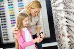 Mother help her girl to choose good frame for eyeglasses royalty free stock images