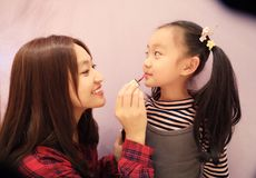 Mother helped her daughter make up and smear lipstick. In a shop, shanghai, china royalty free stock photo