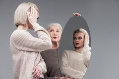 Attentive blonde woman refreshing her bob haircut in round mirror. Mother helping. Attentive blonde women refreshing her bob haircut in round mirror while senior royalty free stock photography