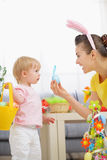 Mother helping baby collecting Easter eggs Stock Photo