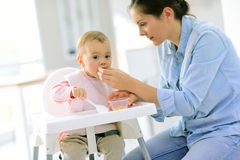 Mother helping baby girl eating on high chair Royalty Free Stock Image
