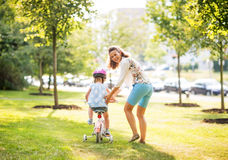 Mother helping baby girl riding on bicycle Stock Images
