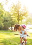 Mother helping baby girl riding bicycle outdoors Stock Photo