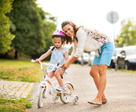 Mother helping baby girl riding bicycle Royalty Free Stock Images