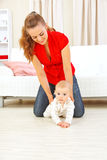 Mother helping baby learn to creep. Smiling mother helping cheerful baby learn to creep Royalty Free Stock Photos