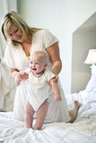 Mother helping baby learn to walk Royalty Free Stock Photo