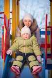 Mother helping baby to slide down on playground. In winter Stock Image