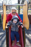 Mother helping baby to slide down on playground Stock Photo