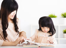 Mother  helping child daughter to reading Stock Photos