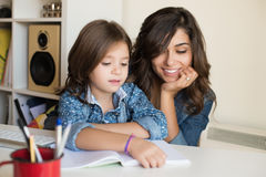 Mother helping child with homework Royalty Free Stock Image
