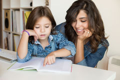 Mother helping child with homework Stock Images