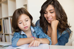 Mother helping child with homework Royalty Free Stock Images