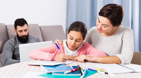 Mother helping child to do homework stock images
