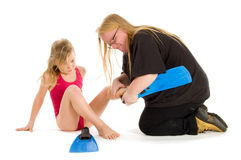 Mother helping child to put on flippers Royalty Free Stock Photos