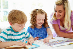 Mother Helping Children With Homework In Kitchen Royalty Free Stock Images