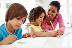 Mother Helping Children With Homework In Kitchen. Pointing To Book Smiling Royalty Free Stock Photography