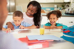 Mother Helping Children With Homework At Table Royalty Free Stock Photo