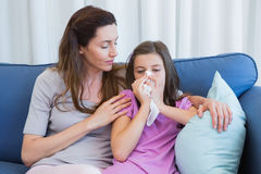 Mother helping daughter blow her nose Royalty Free Stock Images