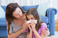 Mother helping daughter blow her nose Stock Photography