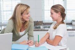 Mother helping daughter doing homework Stock Image