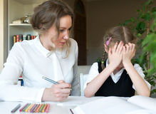 Mother helping daughter with homework. Royalty Free Stock Photos