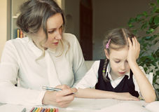 Mother helping daughter with homework. Royalty Free Stock Photography