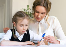 Mother helping daughter with homework. Stock Photos