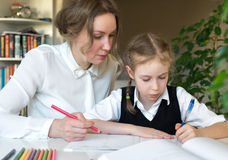 Mother helping daughter with homework. Royalty Free Stock Photo