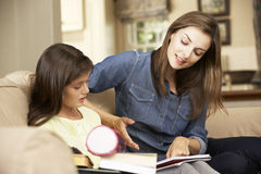 Mother Helping Daughter With Homework Sitting On Sofa At Home Stock Image