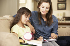 Mother Helping Daughter With Homework Sitting On Sofa At Home Stock Photos