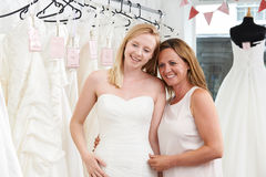 Mother Helping Daughter To Choose Dress In Bridal Store Royalty Free Stock Photos