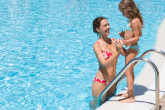 Mother helping daughter to go to the pool. Royalty Free Stock Image