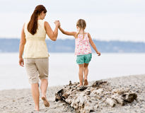 Mother helping daughter walk on log at beach Royalty Free Stock Image
