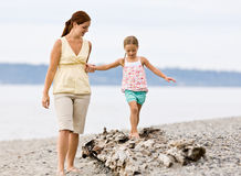 Mother helping daughter walk on log at beach Royalty Free Stock Photography
