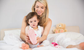 Mother helping daughter in wearing her shoe on bed Stock Images
